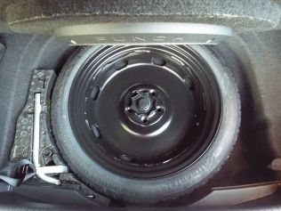 This photo shows the cutout in the rear trim panel which allows the spare tire to lift straight out...
