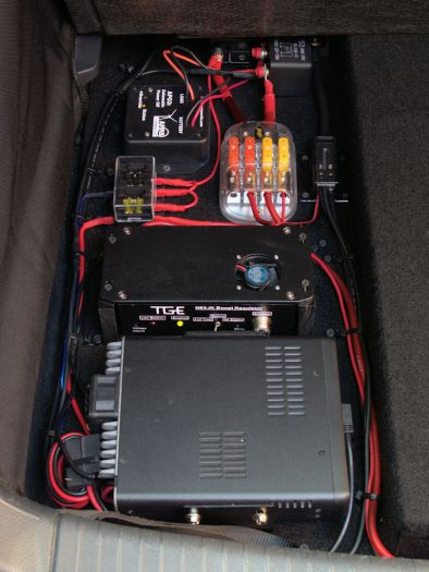 """Clockwise from bottom: VHF/UHF digital transceiver, """"Super Booster,"""" low current fuse box, APO3, 120A relay, high current fuse block, ground block."""